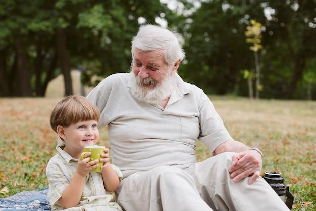 Wnuk z dziadkiem pije herbatę