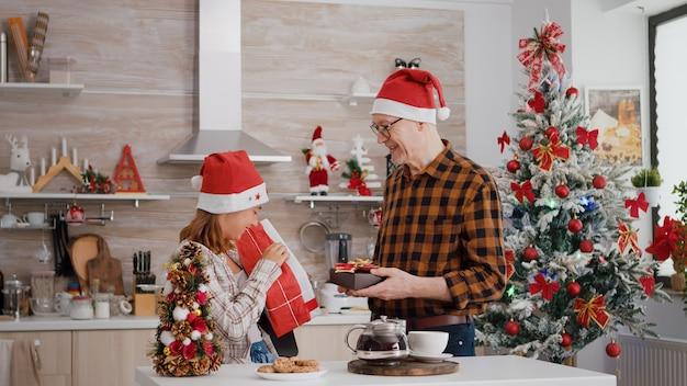 Wnuk z dziadkiem przynoszący prezent ze świątecznym opakowaniem ze wstążką