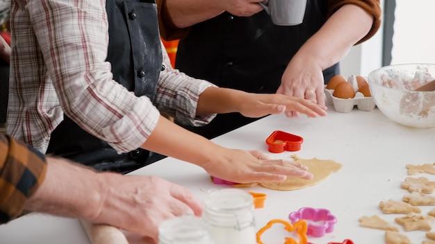Wnuk za pomocą kształtów ciasteczek robi tradycyjne ciasto piernikowe przygotowując deser