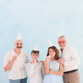 Wnuki dmuchające na rożek ze dziadkami trzymającymi rekwizyty