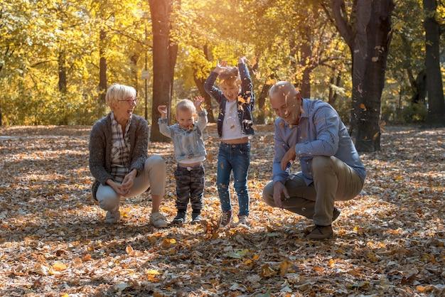 Wnuki i dziadkowie rzucają liście w parku i wspólnie spędzają czas