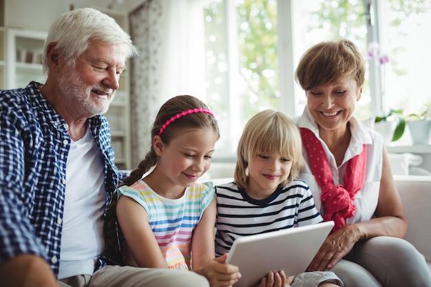 Wnuki za pomocą cyfrowego tabletu z dziadkami