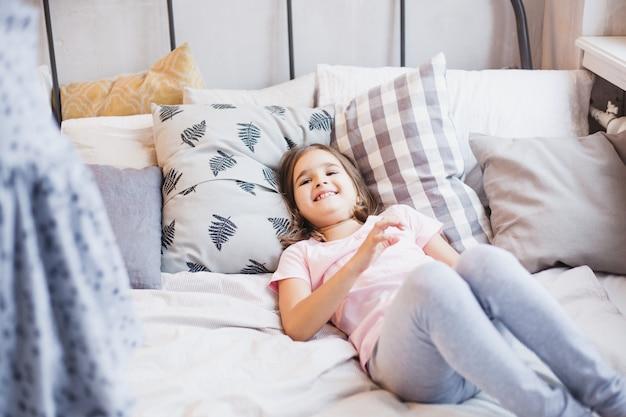 Wo dziewczynki, siostry walczące z poduszkami na łóżku, okno ozdobione świątecznym wieńcem, życie, dzieciństwo