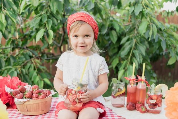 Woda detoksowana z truskawkami i miętą. truskawkowa lemoniada z lodem i miętą jako letni orzeźwiający napój w słoikach. zimne napoje bezalkoholowe z owocami.