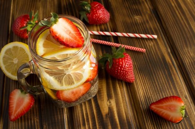 Woda detoksykująca z chia, truskawką i cytryną na drewnianym stole