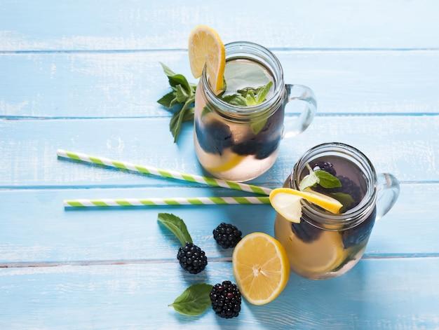 Woda detoksykująca z jeżyną i cytryną w szklanych słoikach