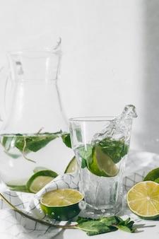 Woda detoksykująca z owocami limonki i liśćmi mięty. świeża domowa lemoniada miętowa.