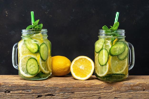 Woda detoksykująca z pokrojoną cytryną i ogórkiem w słoiku w ciemności.
