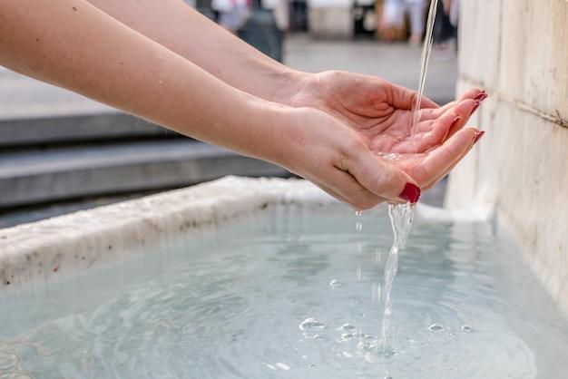 Woda działa w fontannie pitnej w parku w letni dzień. młoda kobieta pitnej wody z fontanny. więc odświeżanie