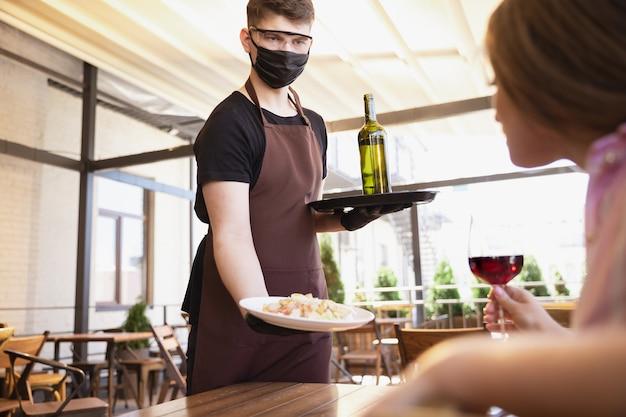 Woda działająca z maską na twarz w restauracji, epidemia koronawirusa