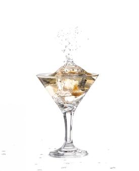 Woda faluje i rozpryskuje się, gdy do szklanki wrzuca się zieloną hiszpańską oliwkę z pieprzem