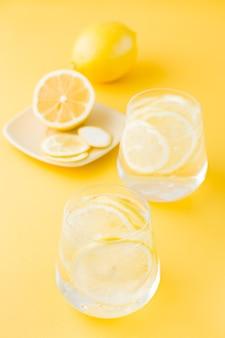 Woda gazowana z cytryną i lodem w szklankach i plasterki cytryny na spodku na żółtym