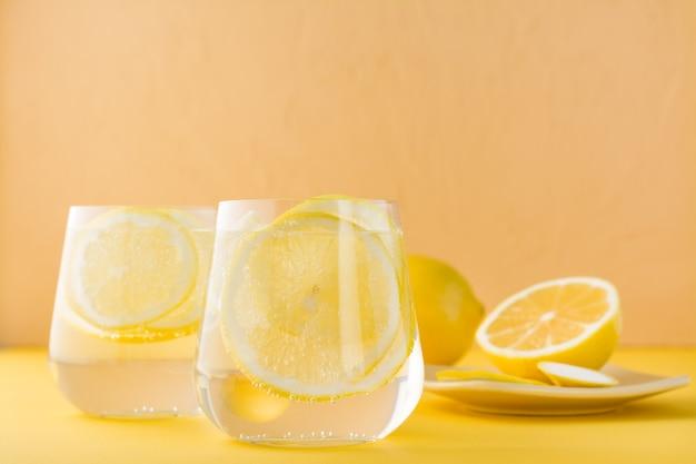 Woda gazowana z cytryną i lodem w szklankach na żółtym stole.