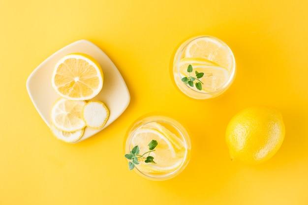 Woda gazowana z cytryną, melisą i lodem w szklankach i plasterkami cytryny na spodku na żółtym stole. napój alkoholowy twardy seltzer. widok z góry