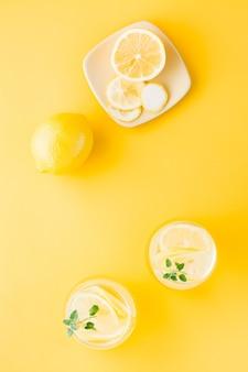 Woda gazowana z cytryną, melisą i lodem w szklankach i plasterkami cytryny na spodku na żółtym stole. napój alkoholowy twardy seltzer