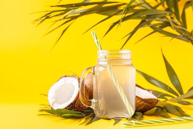 Woda kokosowa i orzechy kokosowe na jasnym pastelu