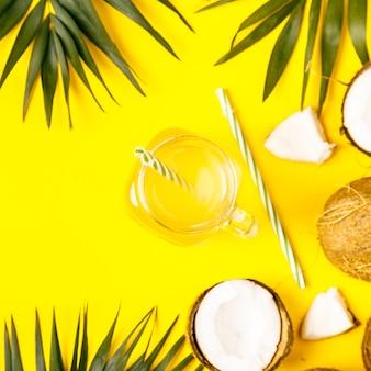 Woda kokosowa i orzechy kokosowe z tropikalnymi liśćmi.