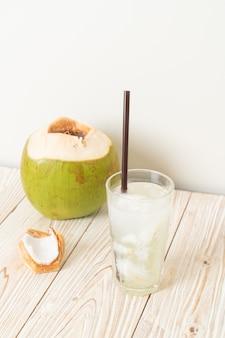 Woda kokosowa lub sok kokosowy w szklance z kostką lodu
