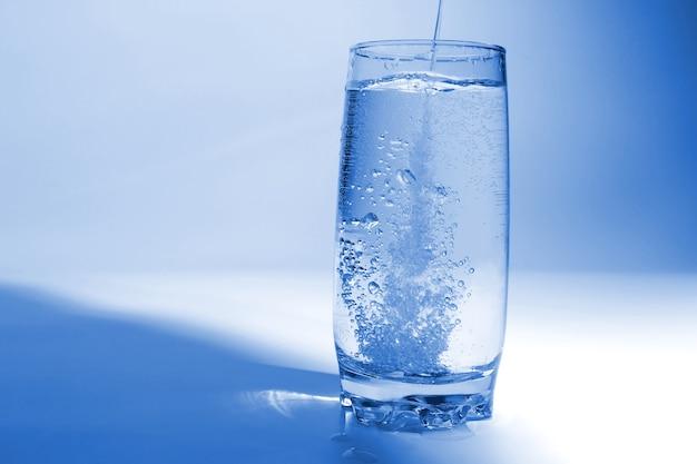 Woda leje się w przezroczystym szkle z bąbelkami powietrza