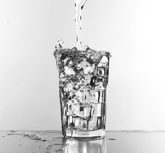 Woda leje się w szkle na białym tle