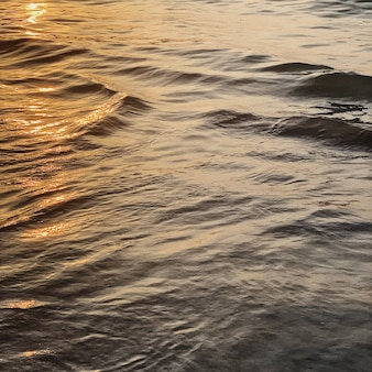 Woda morska lub oceaniczna z małymi relaksującymi falami i odbiciem kolorowego pomarańczowego zachodu słońca