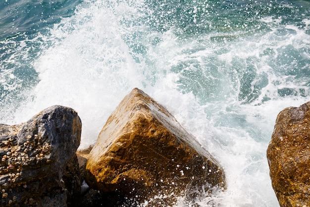 Woda morska uderza o skaliste skały i tworzy fale z pianą, chropowaty molo w morzu