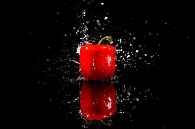 Woda musująca spada na pyszne czerwoną papryką, która stoi na czarnym stole