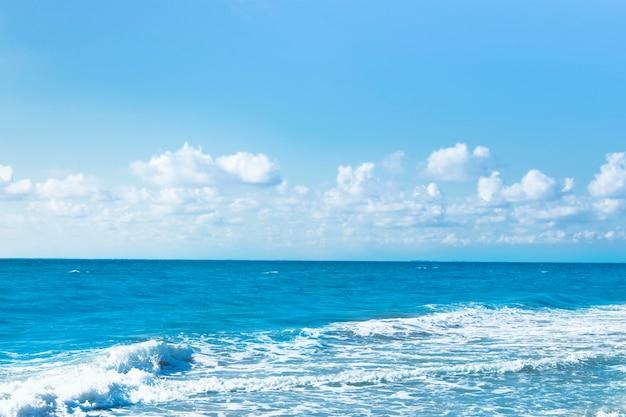 Woda oceanu z niebieskim niebem z chmurami.