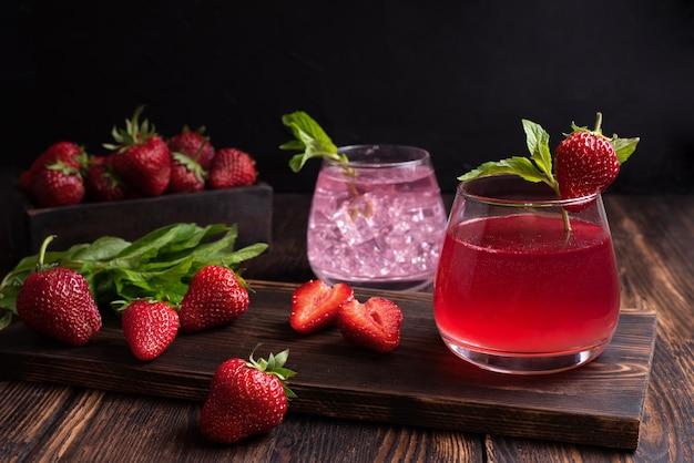 Woda owocowa, lemoniada truskawkowa z gałązką mięty z truskawkami na drewnianym tle, koncepcja lato orzeźwiające napoje, z bliska.