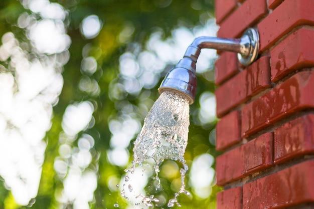 Woda płynie pod prysznicem na ścianie z czerwonej cegły, prysznic na zewnątrz po kąpieli w morzu.