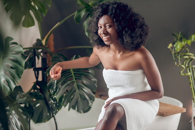 Woda, przyjemność. śliczna szczęśliwa afroamerykanka w białym ręczniku kąpielowym dotyka wody ręką w łazience