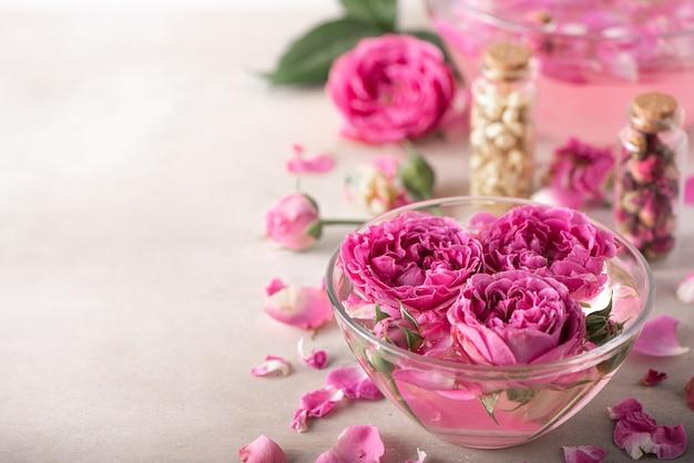 Woda różana w szklanej misce z płatkami i świeżymi kwiatami
