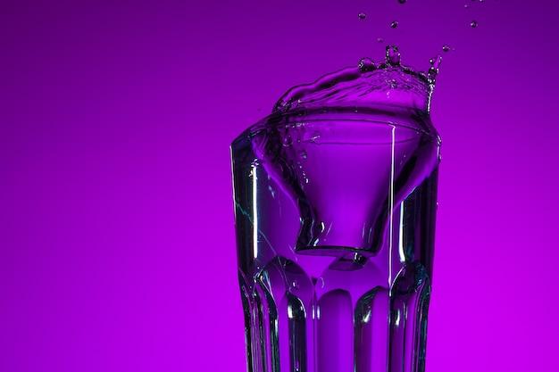 Woda rozpryskująca się w szkle na liliowym tle