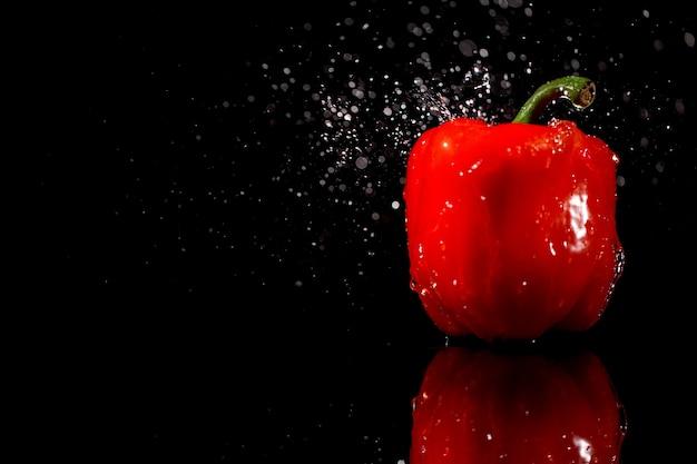 Woda spada na mokrej czerwonej papryki, która stoi na czarnym tle
