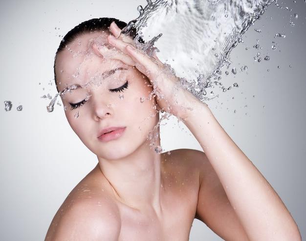 Woda spada na twarz pięknej zmysłowości kobiety z czystą skórą