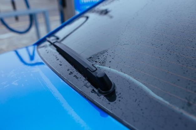 Woda spada na tylną szybę samochodu. koncepcja myjni samochodowej