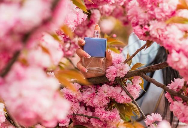 Woda toaletowa. luksusowy balsam. najlepsze marki perfum. przewodnik po perfumach. kobieta trzymać butelkę. projekt rabatu sezonowego z kwiatami wiśni i płatkami. butelka perfum kobieta. wiosenny zapach perfum.