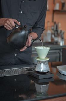 Woda w czajniku spływa do filtra kroplowego.