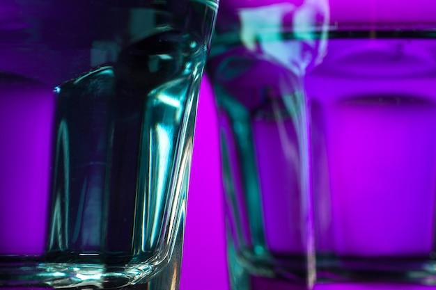 Woda w dwóch szklankach na liliowym tle