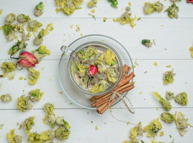 Woda w filiżance z suszonymi ziołami, laski cynamonu widok z góry na drewnianym stole