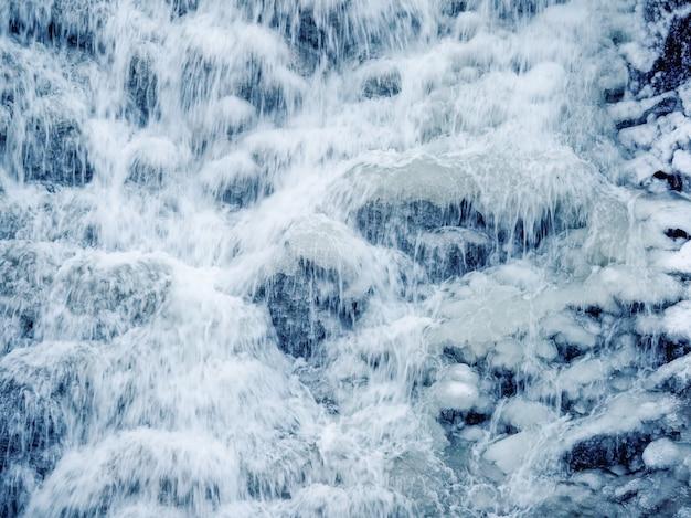 Woda w ruchu. kaskady wodospadu w zimie z bliska
