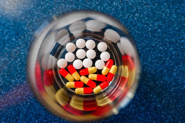 Woda w szklanym kubku i porcja tabletek w drugiej szklance na niebieskiej powierzchni