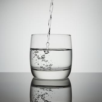 Woda wlewa się do szkła. przezroczysty strumień wody wpadający do szklanki. rozpryski, krople, pęcherzyki powietrza ze strumienia wodnego.