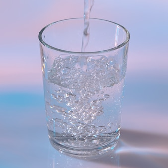Woda wlewa się do szklanki na białym tle z neonowymi światłami