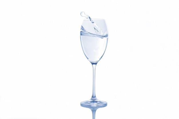 Woda wlewająca się do przezroczystego szkła z bąbelkami powietrza