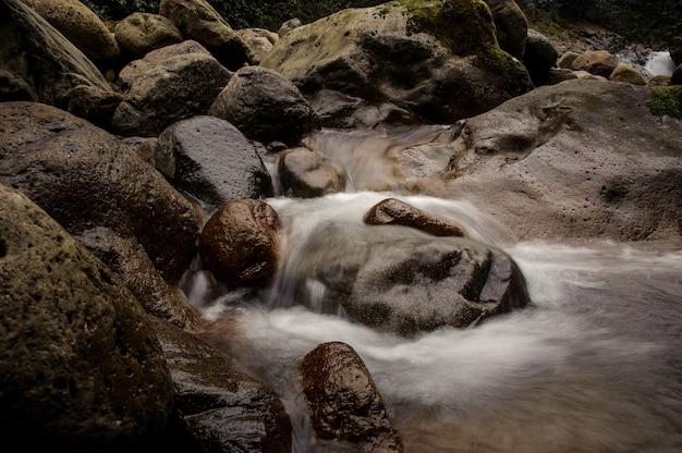 Woda wpadająca do jeziora otoczonego skałami w łaźniach afrodyty w gruzji
