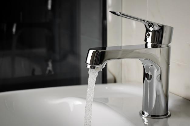 Woda wypływa z kranu lub kranu w łazience. skopiuj przestrzeń, z bliska