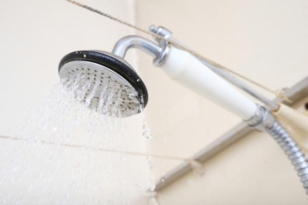 Woda wypływająca ze starej słuchawki prysznicowej z ceramiczną rączką z kamieniem wymagała wymiany lub odkamieniania.