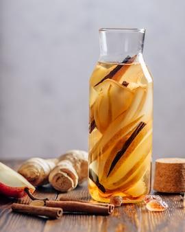Woda z dodatkiem gruszki, korzenia imbiru i laski cynamonu. niektóre składniki na stole.
