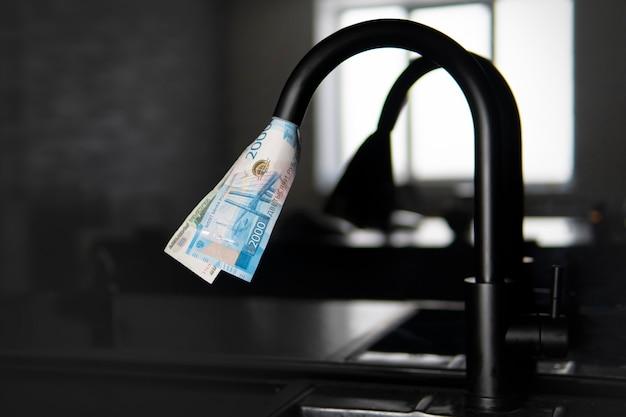 Woda z kranu wypluwa dolary amerykańskie. drogie zaopatrzenie w wodę. koncepcja podniesienia ceny usług użyteczności publicznej dla ludności. drogie ciepłej i zimnej wody w domu.